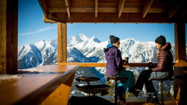 Two women drink coffee and look at the vast view of the mountains from the deck of the Elkhorn Cabin at Panorama Mountain Resort